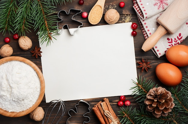 クリスマスのベーキング成分、クッキーカッター、スパイス、ベリー、卵、暗い木製の小麦粉