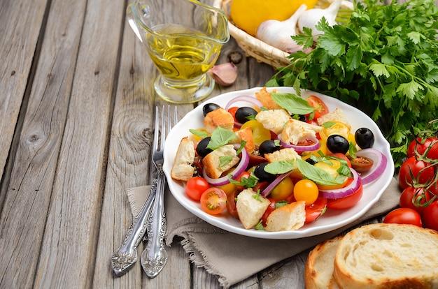 新鮮なトマトと素朴な木製のテーブルにシャキッとしたパンと伝統的なイタリアのパンザネラサラダ。