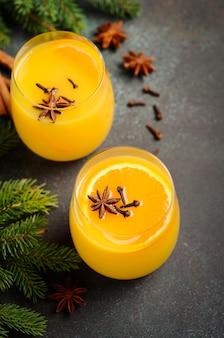 秋冬カクテルホットスパイシーオレンジパンチとスパイス。モミの枝とスパイスで飾られた休日の概念。