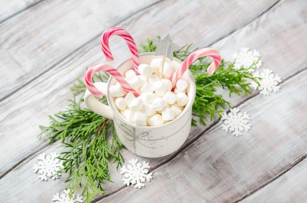 新年やクリスマス。マシュマロと木製の背景にキャンディー杖と組成。