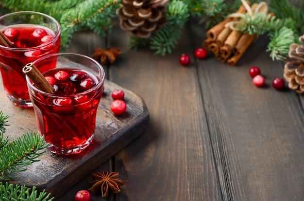 Рождественский глинтвейн. концепция праздника украшен еловыми ветками, клюквой и специями.