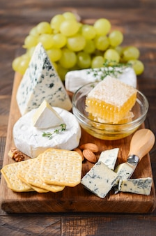 ブドウ、クラッカー、蜂蜜、木製のテーブル上のナッツとチーズプレート