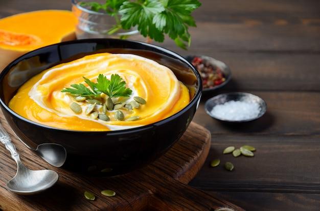 木製のテーブルにクリームとカボチャの種とカボチャのクリームスープ