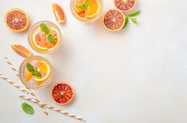 Холодный освежающий напиток с кусочками апельсина крови в стакане на белом бетоне вид сверху, плоская планировка, копия пространства.