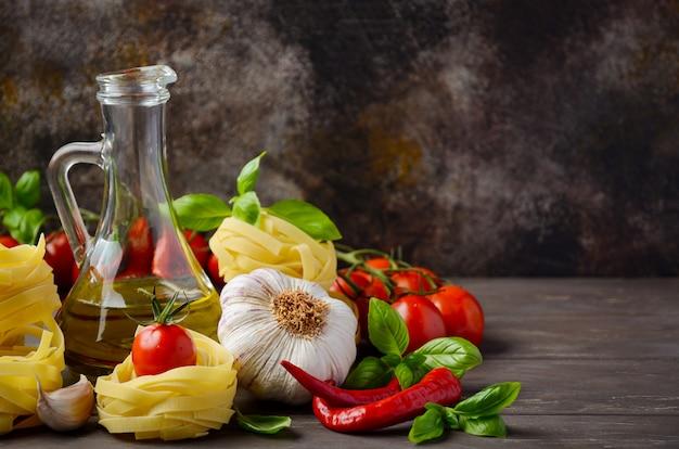 木製テーブルの上のイタリア料理のパスタ、野菜、ハーブ、スパイス。