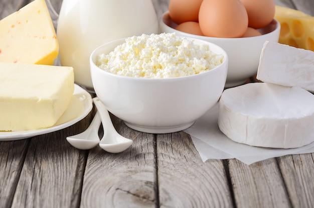 新鮮な乳製品。牛乳、チーズ、ブリーチーズ、カマンベール、バター、カッテージチーズ、木製のテーブルの卵。