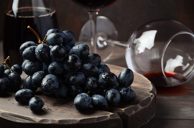 Свежий черный виноград и красное вино на деревянный стол