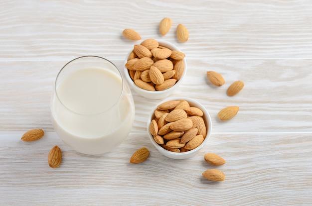 Миндальное молоко и миндаль на белом деревянном