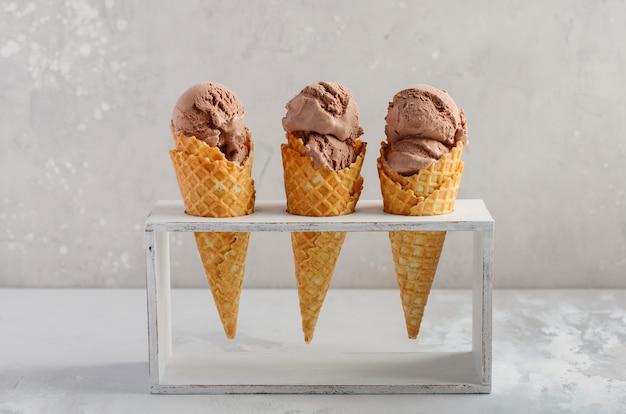 Шоколадное мороженое в вафельном рожке на сером бетоне