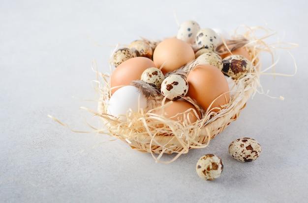 灰色のコンクリートテーブルの上のバスケットに卵の種類