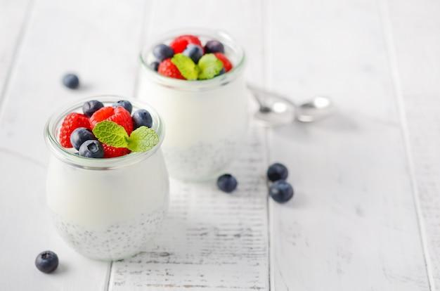 白い木製のテーブルに新鮮な果実とチア種子プディング。