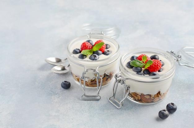 自家製グラノーラとガラスの瓶に新鮮な果実、健康的な朝食のコンセプトとヨーグルトのパフェ