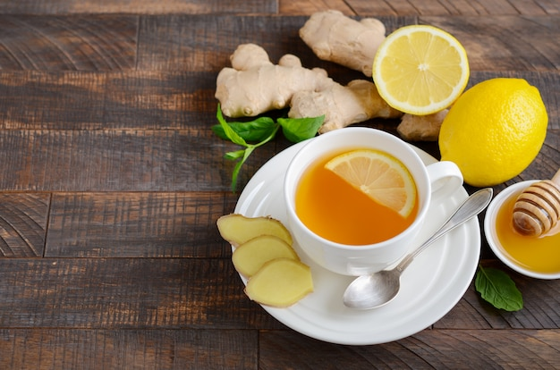 レモンと木製のテーブルの上に蜂蜜とジンジャールートティー。