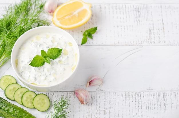Греческий соус дип или соус цацики украшен оливковым маслом и мятой на белом деревянном столе.