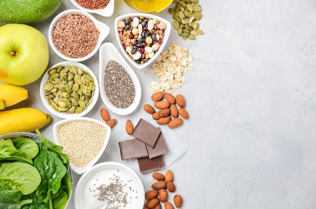 健康食品栄養ダイエットコンセプト。バナナ、チョコレート、ほうれん草、アボカド、リンゴ、キノア、チア、亜麻の種子、ヨーグルト、アーモンド、豆、オート麦、カボチャの種、オリーブオイル。