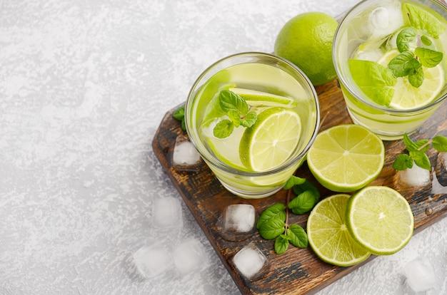 Холодный освежающий летний напиток с лаймом и мятой в стакане на сером бетонном или каменном столе.