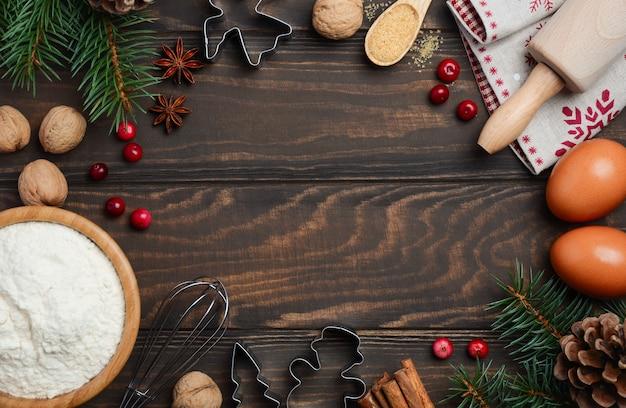 Рождественские выпечки ингредиенты на темном фоне древесины, вид сверху, квартира лежал, скопируйте пространства.