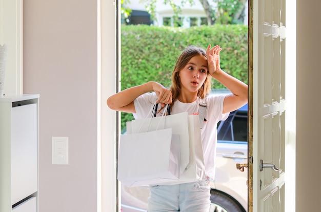 美しい若い女の子が彼女の手の中にショッピングバッグを持って帰って家に帰って疲れた