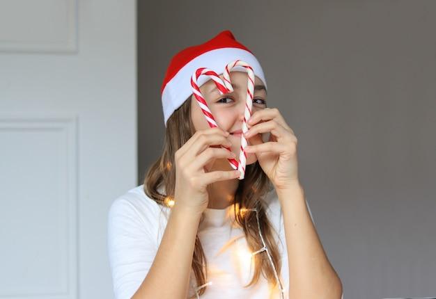 Портрет счастливой девушки в красной шапке санта-клауса, глядя через сердце рождественской трости