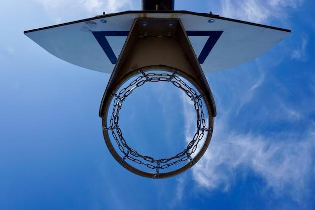 バスケットボールフープと路上で青い空