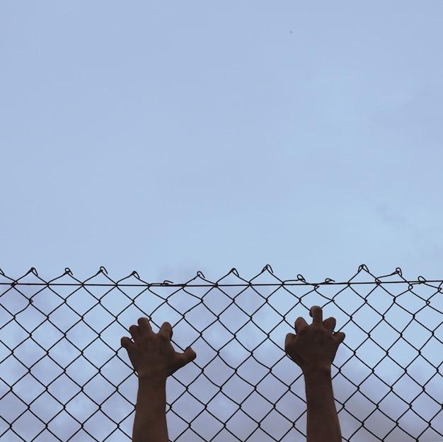 通りの金属フェンスをつかむ男の手