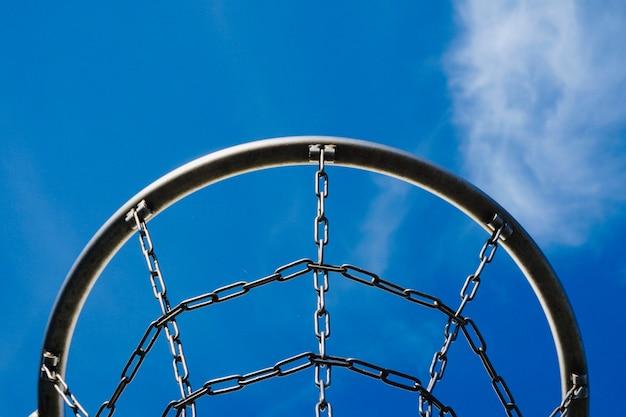 路上で金属ネットと青空とバスケットボールフープ