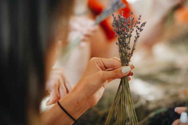 花屋の女の子の手の中に乾燥ラベンダーの花束