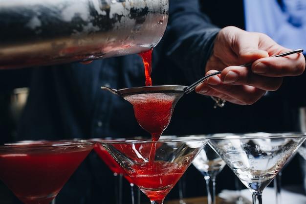 バーで赤いカクテルを作る専門のバーテンダーのクローズアップ