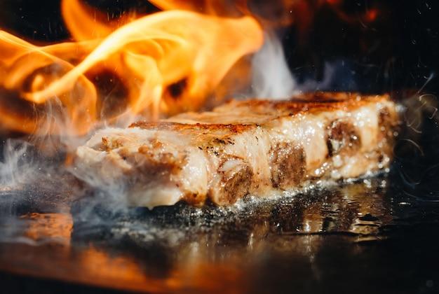 Великолепные аппетитные свиные ребрышки барбекю на гриле в огне.