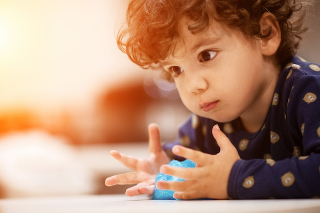 Маленький странный мальчик играет со спамом в своей комнате