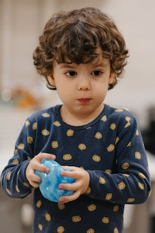 Маленький странный мальчик играет со слизью в своей комнате