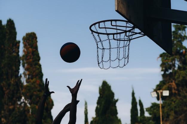 ストリートバスケットボールの試合。シールド、バスケットにボールが飛ぶ。バスケットボールリングの正確なスロー。スポーツの概念。