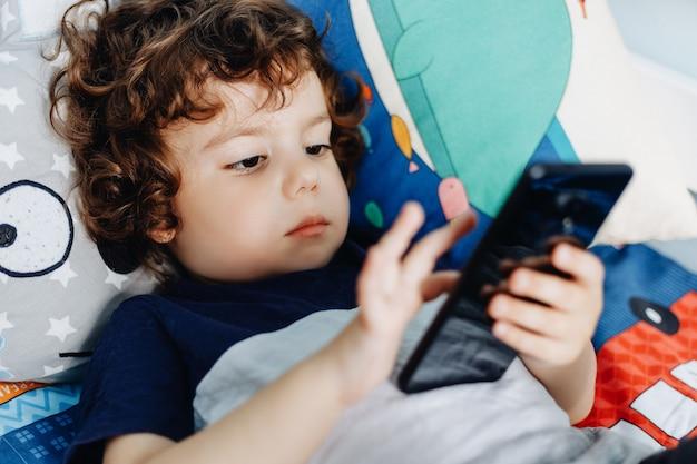 Вау, мне нравится этот телефон ребенок с смартфона. мальчик сидя в кровати и играя с мобильным телефоном. звоню моей маме. милый маленький ребенок держит мобильный телефон в руках и внимательно смотрит на экран.