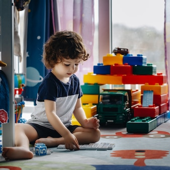 Маленький ребенок играет в домино в своей комнате на полу