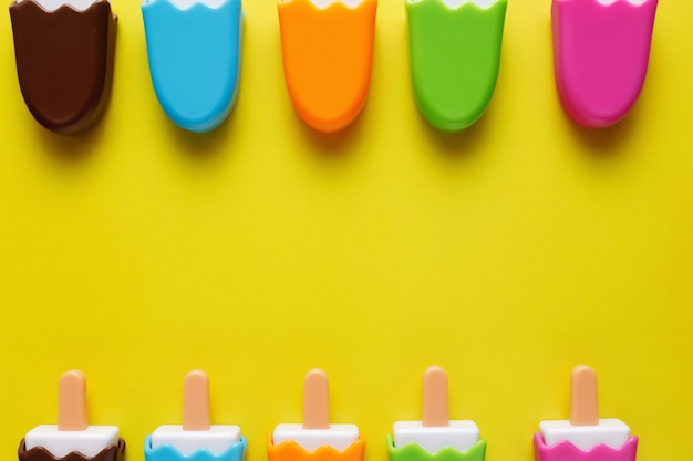 黄色の背景に赤ちゃんの番号を持つカラフルで様々なプラスチック製のおもちゃのアイスクリーム。