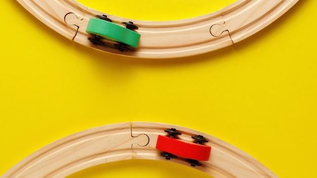 黄色の背景、おもちゃの木製の鉄道や電車の子供のおもちゃフレーム。上面図。フラットレイ。テキストのスペースをコピー