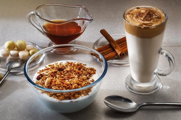 ダルゴナコーヒー、ミューズリー、ライトテーブルの蜂蜜高速おいしい朝食。