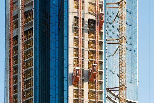 建設現場で作業員や資材を持ち上げるために使用される乗客用ホイストリフト。