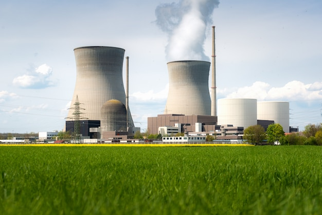 黄色のフィールドと大きな青い雲と原子力発電所。