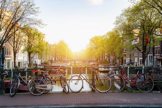 日没時にアムステル川を望むオランダのアムステルダム運河を自転車で走行します。