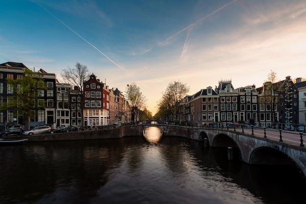 アムステルダム、日没時にアムステル川とオランダのシティービュー。