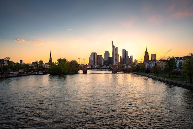フランクフルトはドイツのフランクフルトで日没時に建物の高層ビルと主要都市のスカイラインです。