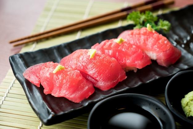 Суши из тунца на черной тарелке с японским соусом и зелеными листьями.