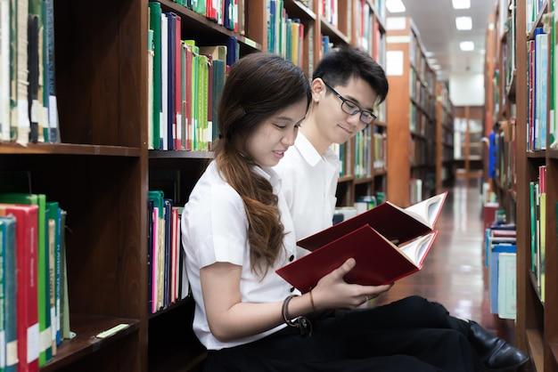 アジアのカップル学生が図書館で勉強しているの肖像画。