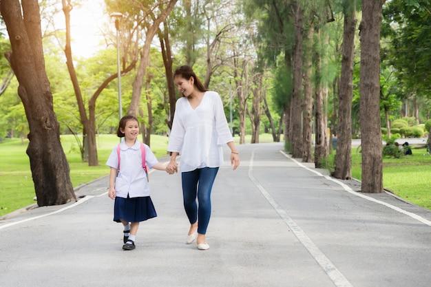 アジアの母と娘の学生が学校に歩いています。