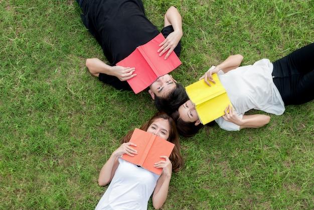 Взгляд сверху группы в составе азиатский студент лежа с тетрадью и смотря прочь.