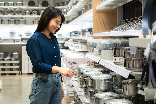 アジアの女性はモールで新しい台所用品を購入することを選択しています