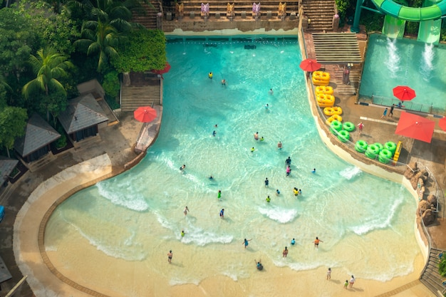 シンガポールのセントーサにある多くの旅行者がいるウォーターパークのトップビューには、楽しいスイミングプールがあります。