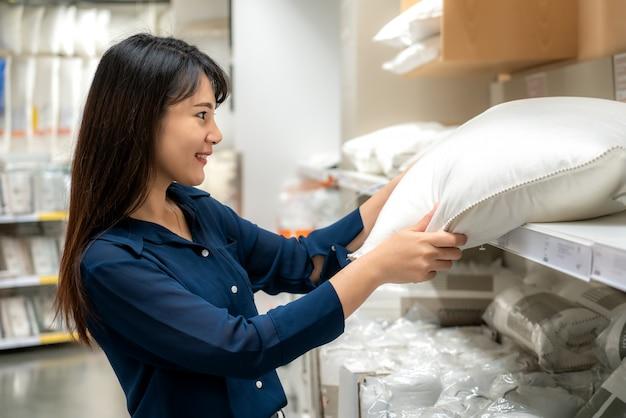アジアの女性はモールで新しい枕を買うことを選択しています。食料品や家庭用品のショッピング。