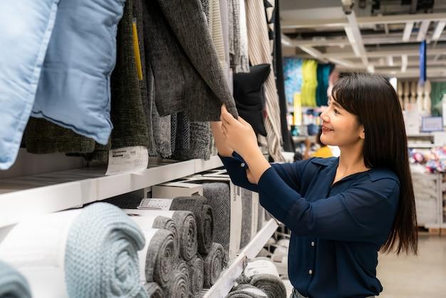 アジアの女性はモールで新しいカーペットを買うことを選択しています。食料品や家庭用品のショッピング。